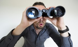 man-looking-through-binoculars-600x360